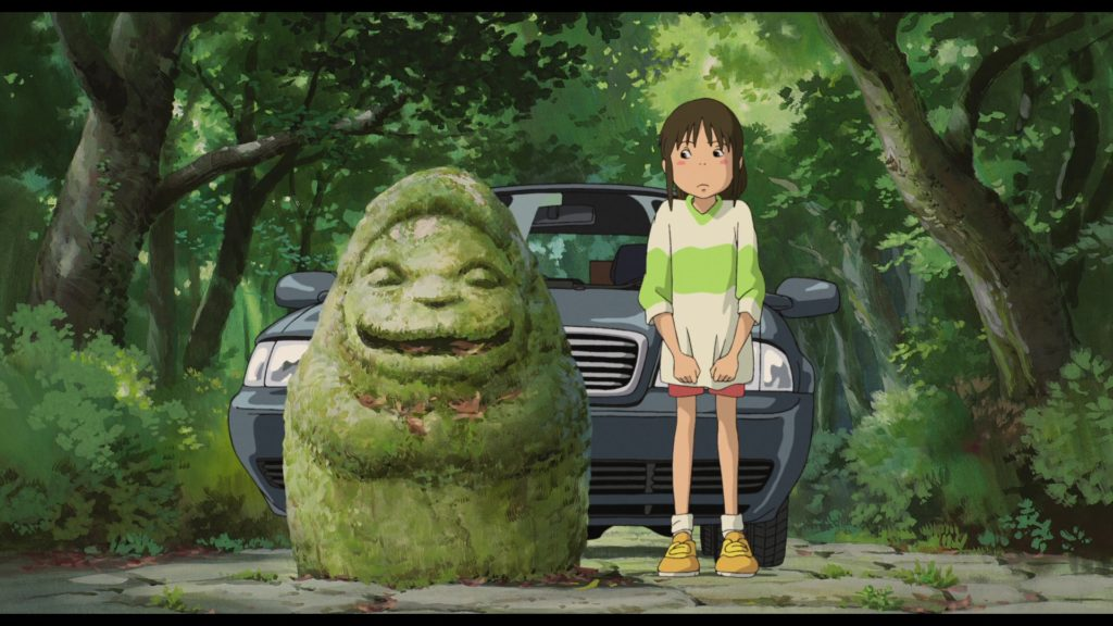 Chihiro looks nervously at the stone idol beside her
